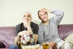 Zwei junge Männer, die eine Fußbalabgleichung auf Fernsehapparat überwachen Stockfotografie