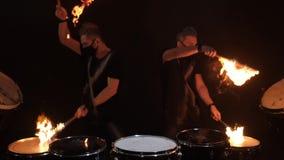 Zwei junge Männer, die Feuertrommel spielen stock footage