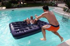 Zwei junge Männer, die im Swimmingpool spielen Stockbild