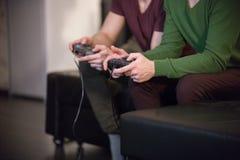 Zwei junge Männer, die Spiele spielend, halten Steuerknüppel lizenzfreie stockfotografie