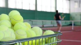 Zwei junge Männer, die Tennis auf Tennisplatz spielen Ein Wagen gefüllt mit Tennisbällen auf einem Vordergrund stock footage