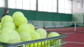 Zwei junge Männer, die Tennis auf Tennisplatz spielen Training Ein Wagen gefüllt mit Tennisbällen auf einem Vordergrund stock footage