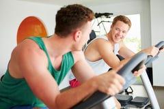 Zwei junge Männer, die zusammen in der Turnhalle auf Radfahrenmaschinen ausbilden Stockfotografie
