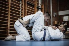 Zwei junge Männer, die zusammen Judo üben Stockbild