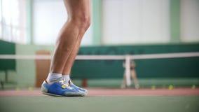 Zwei junge Männer in einem in guter Verfassung, das Tennis spielt Füße in den blauen Stiefeln im Fokus stock video footage