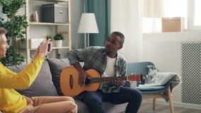 Zwei junge Männer haben den Spaß, der zu Hause Gitarre spielt und Video auf smarthphone notiert stock video footage