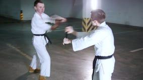 Zwei junge Männer im Kimono ihre Fähigkeiten auf einem Untertageparkplatz ausbildend Klingenkampf stock video