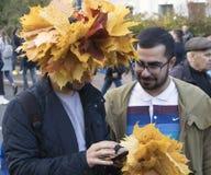 Zwei junge Männer mit Kranz und Blumenstrauß von gelben Ahornblättern lizenzfreie stockfotografie