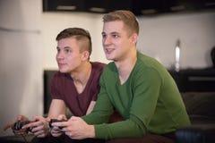 Zwei junge Männer, Spiele am Abend, spielend Steuerknüppel halten lizenzfreies stockfoto