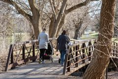 Zwei junge Mütter, die Spaziergänger im Park im Vorfrühling drücken stockfotografie
