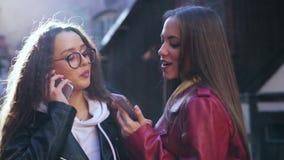 Zwei junge M?dchen, die drau?en intelligente Telefone verwenden Zwei Frauenanteildaten oder -kontakte in den Smartphones stock video