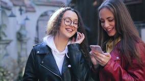 Zwei junge M?dchen, die drau?en intelligente Telefone verwenden Zwei Frauenanteildaten oder -kontakte in den Smartphones stock video footage