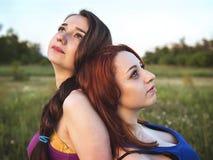 Zwei junge Mädchen auf einem Rest draußen Stockfotos