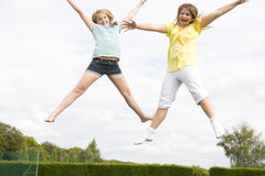 Zwei junge Mädchen, die auf dem Trampolinelächeln springen Stockfotografie
