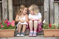 Zwei junge Mädchen, die im hölzernen Haus spielen Stockfoto