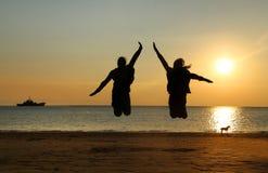 Zwei junge Mädchen, die am Strand springen Stockfotografie