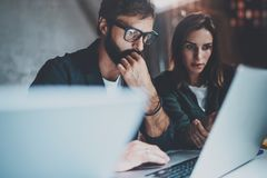 Zwei junge Mitarbeiter, die zusammen an Laptops am modernen coworking Studio nachts arbeiten Tragende Gläser des Mannes unter Ver lizenzfreies stockfoto