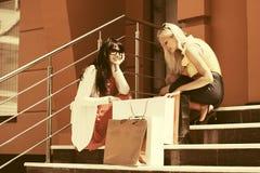 Zwei junge Modefrauen mit Einkaufstaschen auf dem Mall tritt Stockfotografie
