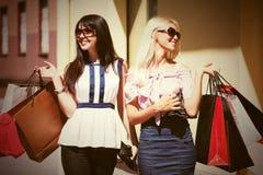 Zwei junge Modefrauen mit Einkaufstaschen gehend in Stadt stree Stockbild