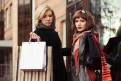 Zwei junge Modefrauen mit Einkaufstaschen im Einkaufszentrum Stockbild