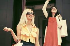 Zwei junge Modefrauen mit Einkaufstaschen im Einkaufszentrum stockfotos