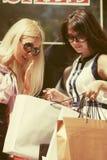 Zwei junge Modefrauen mit Einkaufstaschen im Einkaufszentrum lizenzfreie stockbilder