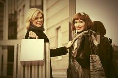 Zwei junge Modefrauen mit Einkaufstaschen nahe bei Malltür Stockbild