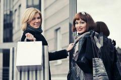 Zwei junge Modefrauen mit Einkaufstaschen nahe bei Malltür Lizenzfreies Stockfoto