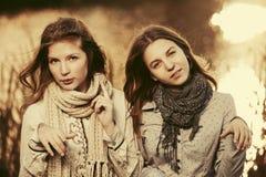 Zwei junge Modemädchen, die durch den See gehen Stockbild