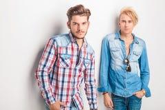 Zwei junge Modemänner, die gegen Studiowand stehen Stockfoto