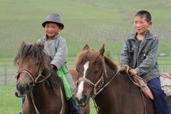 Zwei junge mongolische Reiter Stockfotografie