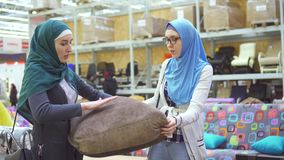 Zwei junge moslemische Frauen wählen ein Sofa in einem Möbelgeschäft stock video