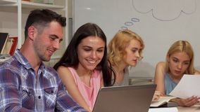 Zwei junge nette Studenten, die ihr Projekt auf dem Laptop besprechen stockfotografie