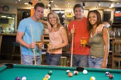Zwei junge Paare, die neben einer Pooltabelle stehen Lizenzfreie Stockfotos