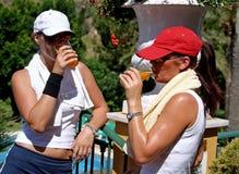 Zwei Junge, Pass-Sitz, gesunde, gebräunte Frauen, die nach einem heißen Spiel von Tennis etwas trinken Stockfotografie