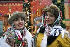 Zwei junge schöne Damen in der traditionellen russischen Kleidung werfen für Fotos auf Stockfotos