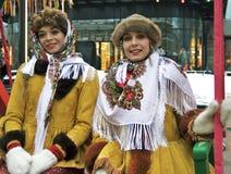 Zwei junge schöne Damen in der traditionellen russischen Kleidung werfen für Fotos auf Lizenzfreies Stockfoto