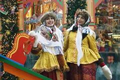 Zwei junge schöne Damen in der traditionellen russischen Kleidung werfen für Fotos auf Lizenzfreie Stockfotografie