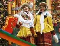 Zwei junge schöne Damen in der traditionellen russischen Kleidung werfen für Fotos auf Stockfotografie