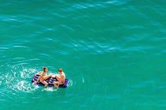 Zwei junge schöne kaukasische Frauen im Bikini ein Sonnenbad nehmend, spritzend und auf Matratze auf ruhigem azurblauem Wasser vo stockfotografie