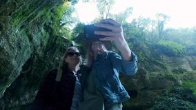 Zwei junge schöne kaukasische Reisendmädchen, die selfie auf einem Smartphone nehmen Angespornt durch die Schönheit der Natur sch stock footage