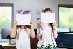 Zwei junge schöne Mädchen, die im Büro stehen, schließen ihr Gesicht mit Papier lizenzfreies stockbild