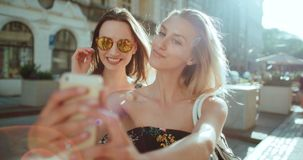 Zwei junge schöne Mädchen, die selfie auf einer Stadtstraße nehmen Lizenzfreie Stockfotografie