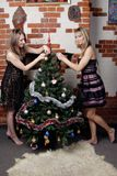 Zwei junge schöne Mädchen verzieren Weihnachtsbaum Stockfotografie