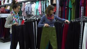 Zwei junge schöne Mädchen wählen Kleidung in einer modernen Butike Mädchen betrachten sorgfältig die Kleidung und überprüfen sie Lizenzfreies Stockbild