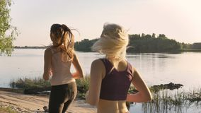 Zwei junge schöne weibliche Läufer, die im Park nahe Fluss rütteln, Eignung modelliert Betrieb, schönen Naturhintergrund stock video