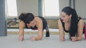 Zwei junge Schönheiten in der Sportkleidung, die in der Stange Innen steht stock video