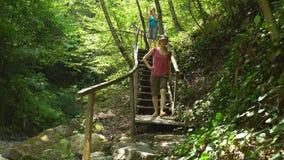 Zwei junge Schönheiten wandern, die unten Treppe im wilden Naturpark des Dschungels in den Bergen kommen Reisetourismuswandern stock footage