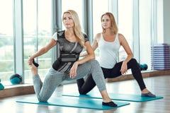 Zwei junge schlanke blonde Frauen, die Übungen in der Turnhalle tun Stockbilder