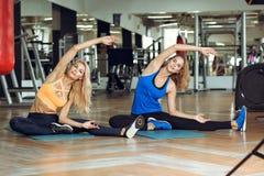 Zwei junge schlanke blonde Frauen, die Übungen in der Turnhalle tun Stockfotografie